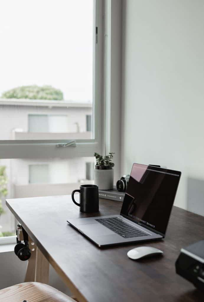 A picture of a desk and laptop in front of a window.
